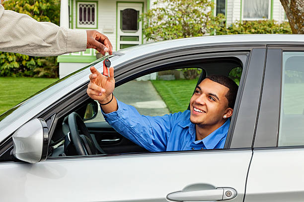 Young Man Borrowing Friend's Car Photo of a young man behind the wheel of a silver sports car, taking the keys from his friend with a smile. borrowing stock pictures, royalty-free photos & images