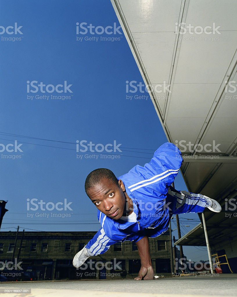 Young man breakdancing, balancing on one hand, portrait royalty-free stock photo