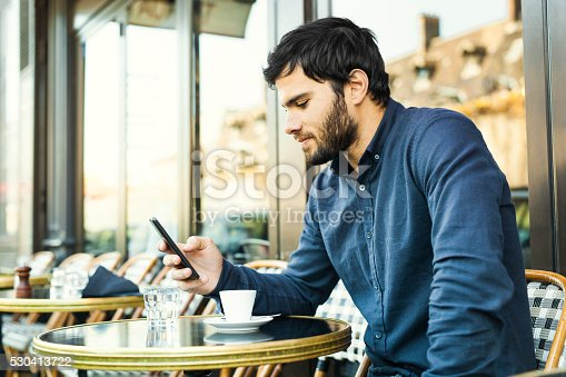 Young good-looking guy with blue shirt, dark hair and beard is reading and replying to messages and posts online on his smartphone while enjoying an espresso coffee in an outdoors cafeteria. He looks relaxed enjoying spending time online. Copy space available. Made in Paris, France.