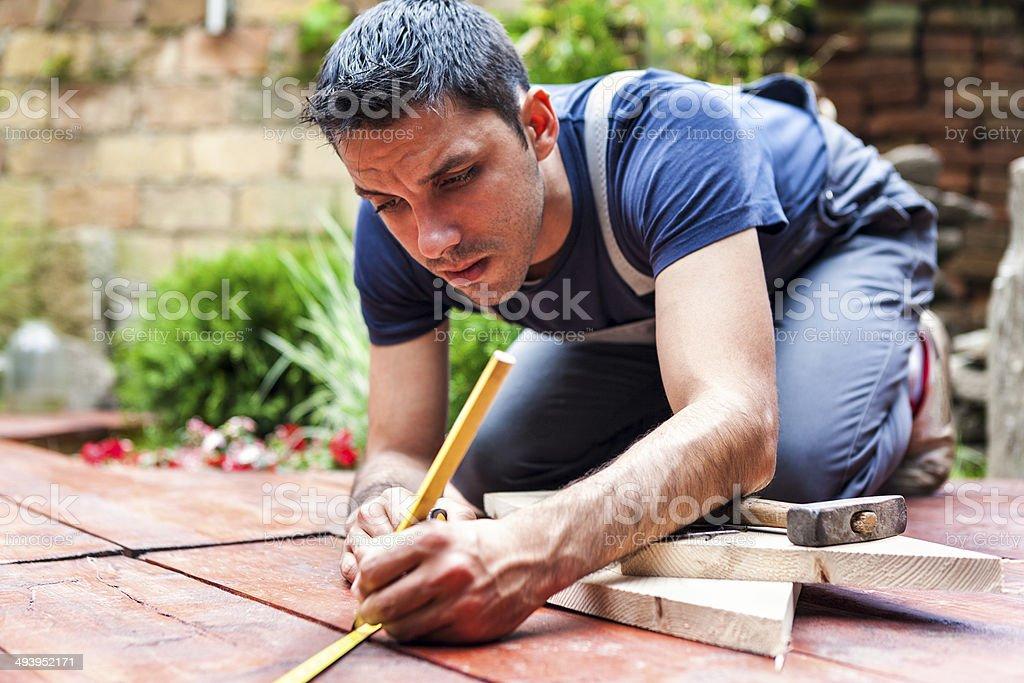 Young man building a backyard deck stock photo