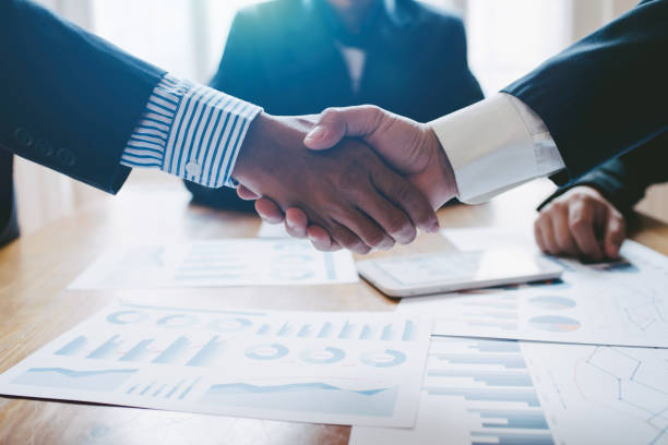 Young man business people shaking hands after brief job for contract signing in modern office with vintage picture style, colleagues at meeting teamwork of partnership. stock photo