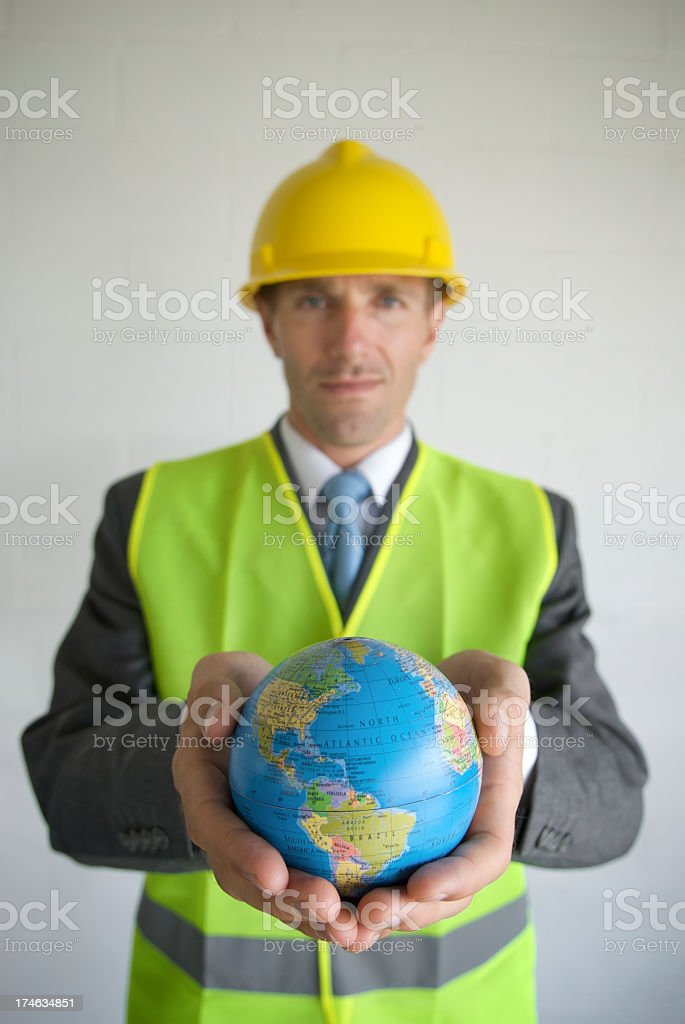 Young Man Businessman Contractor in Hard Hat Holding Globe royalty-free stock photo