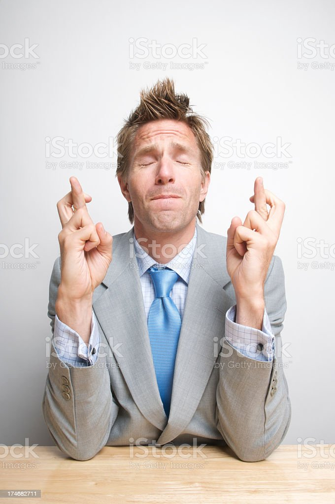 Young Man Businessman Crossing Fingers and Wishing Hard at Desk stock photo