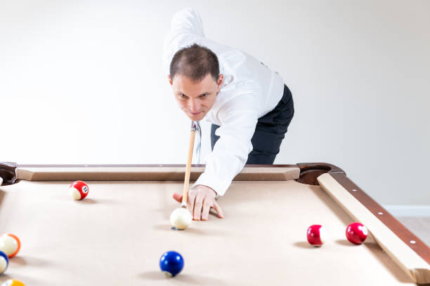 young man, businessman in tie, white shirt, pants holding cue by pool table, playing snooker, billiard, billiards game, ready, striking white ball, many colorful balls in home, house room - pool cue stock photos and pictures
