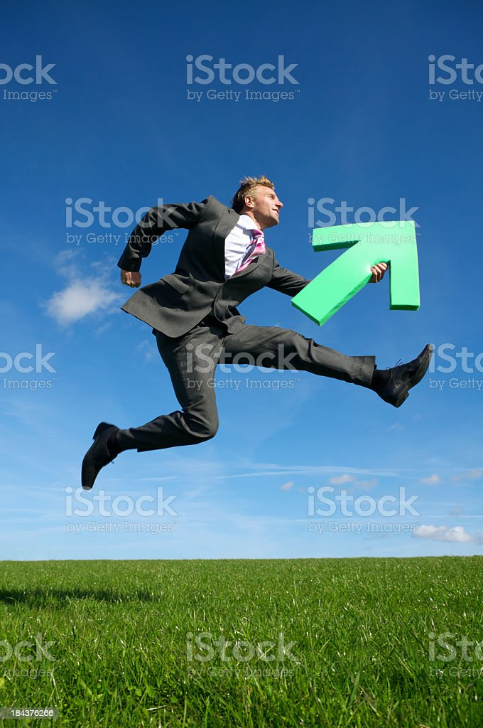 Young Man Businessman Jumping Outdoors Green Arrow Blue Sky Meadow royalty-free stock photo