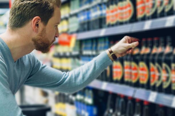young man buying beer - prateleira compras imagens e fotografias de stock