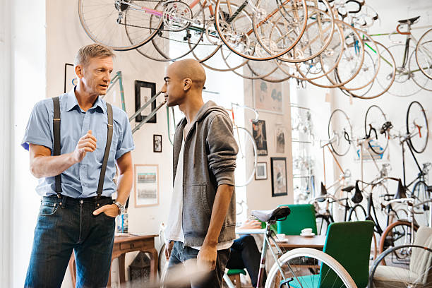 Young Man Buying Bicycle Young man buying a bicycle in a hip bike store. bicycle shop stock pictures, royalty-free photos & images