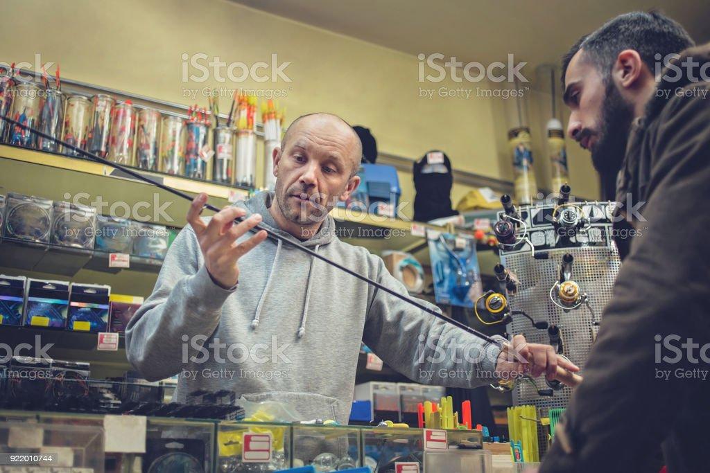 Young man buying fishing rod stock photo