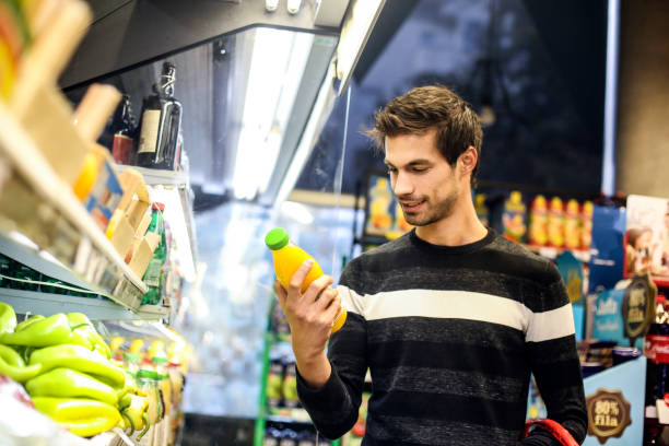 Young man buying juice stock photo