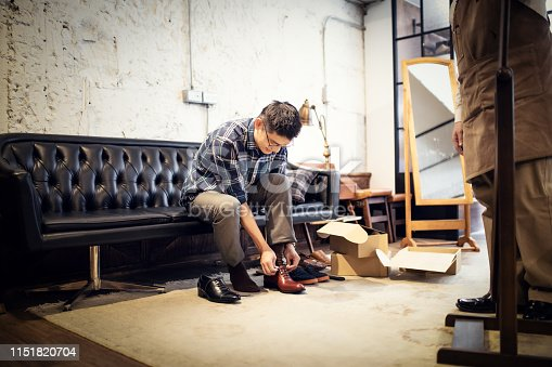 istock Young Man Buying New Shoes 1151820704