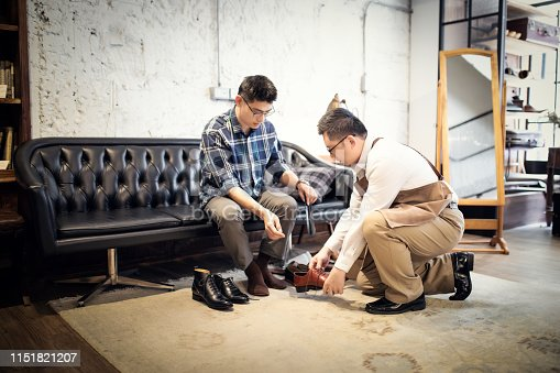 istock Young Man Buying New Shoes 1151821207