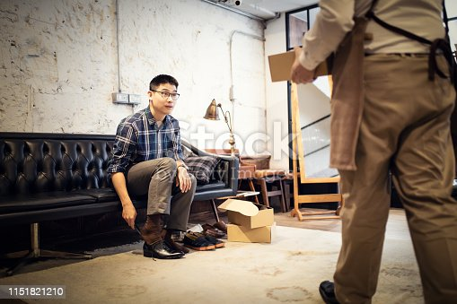 istock Young Man Buying New Shoes 1151821210