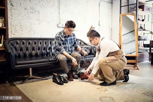 istock Young Man Buying New Shoes 1151821225