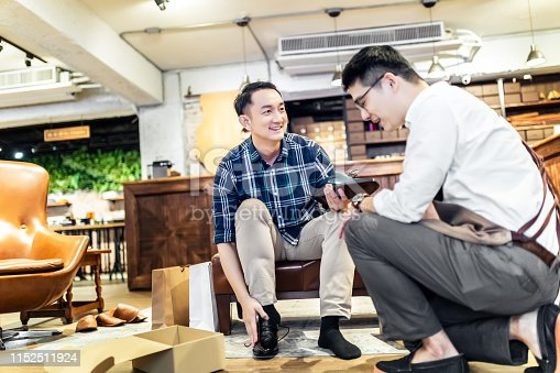 istock Young Man Buying New Shoes 1152511924