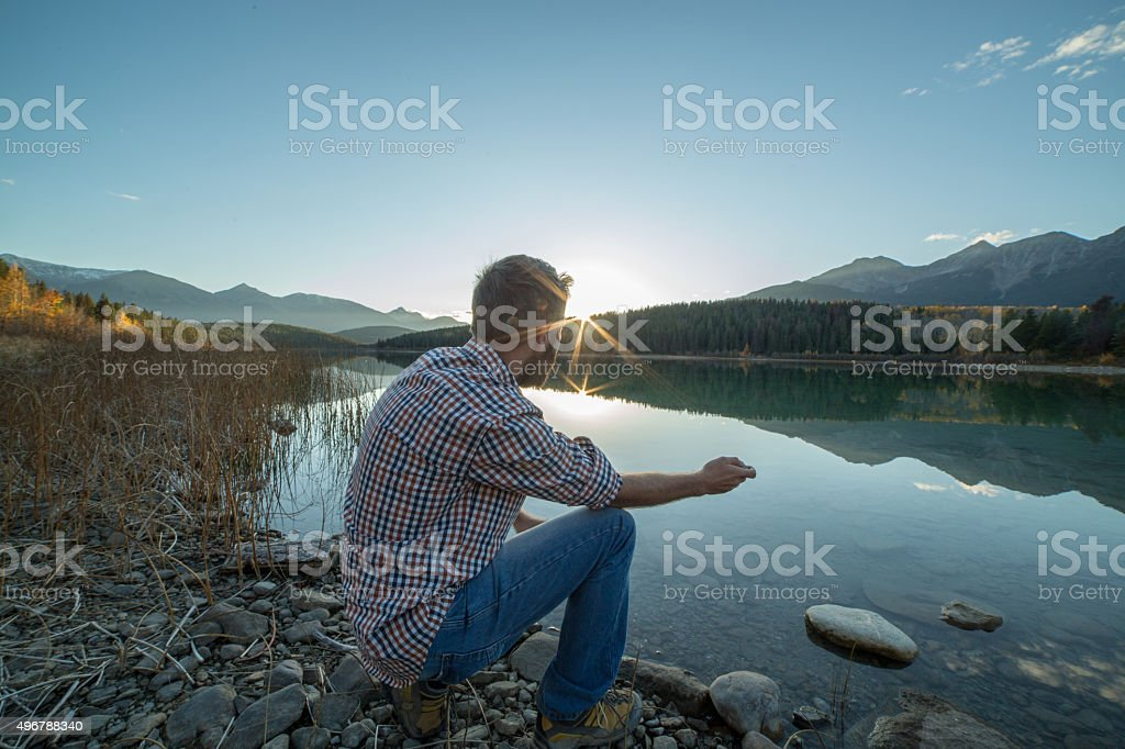 Young man by the lake at sunset skimming stones stock photo