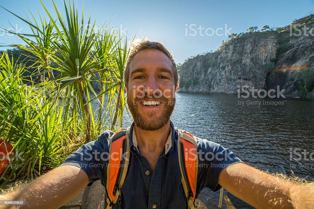 Young man by the lake takes a selfie portrait stock photo