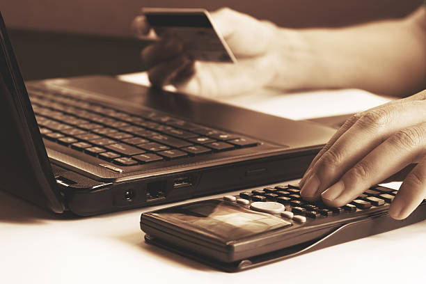 young man calculating and holding credit card with laptop  about - kostenlose onlinespiele stock-fotos und bilder