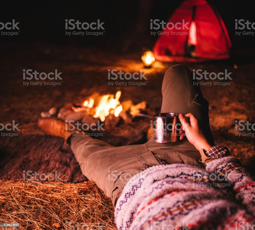 Young man camping and resting at night by campfire stock photo