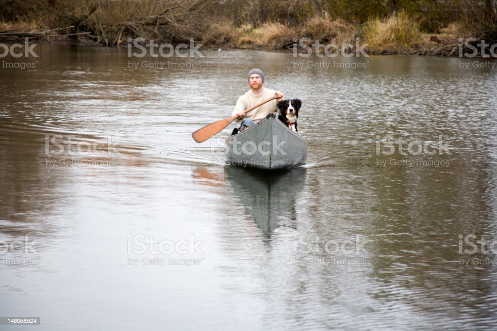Young Man Canoeing With His Dog royalty-free stock photo