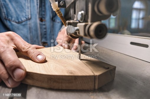 istock young man carpenter builder working with electric jigsaw and wood. 1165176539