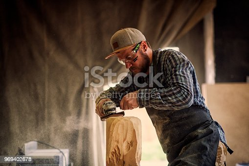 Experienced carpenter in work clothes and small buiness owner working in woodwork workshop, processes the board with an angle grinder on the table is a hammer and many tools