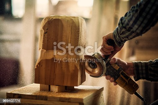 Close up of a  carpenter in work clothes and small buiness owner working in woodwork workshop, processes the board with an angle grinder , on the table is a hammer and many tools
