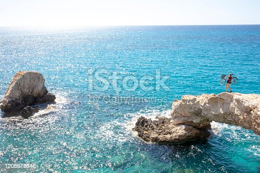 903015102 istock photo Young man carries bicycle over rough coastal terrain 1208678846