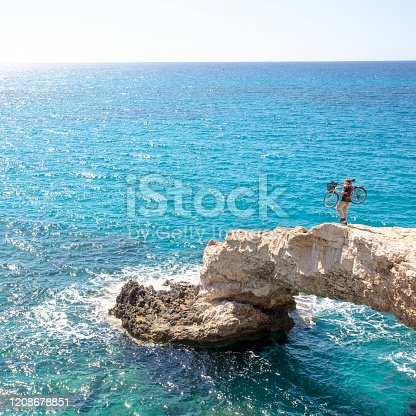 903015102 istock photo Young man carries bicycle over rough coastal terrain 1208678851