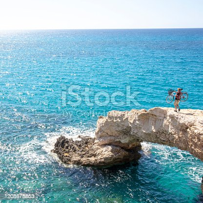 903015102 istock photo Young man carries bicycle over rough coastal terrain 1208678853