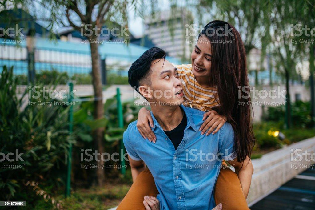 年輕男子背著一個漂亮的女人在他的背上 - 免版稅一起圖庫照片
