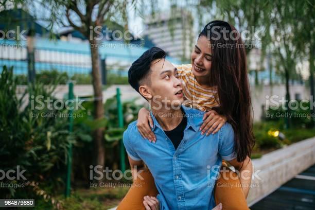 年輕男子背著一個漂亮的女人在他的背上 照片檔及更多 一起 照片