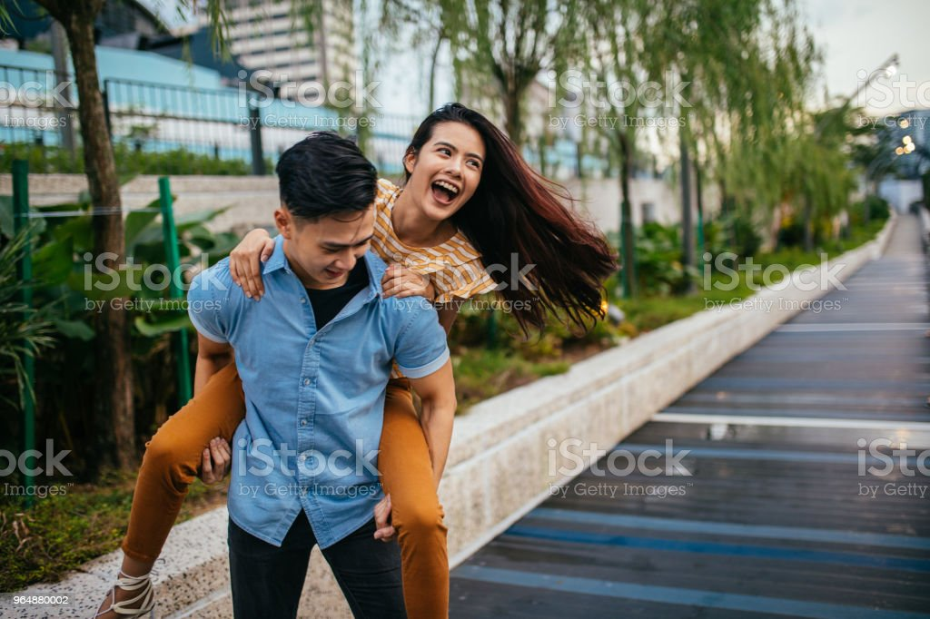 Young man carrying a beautiful woman on his back royalty-free stock photo