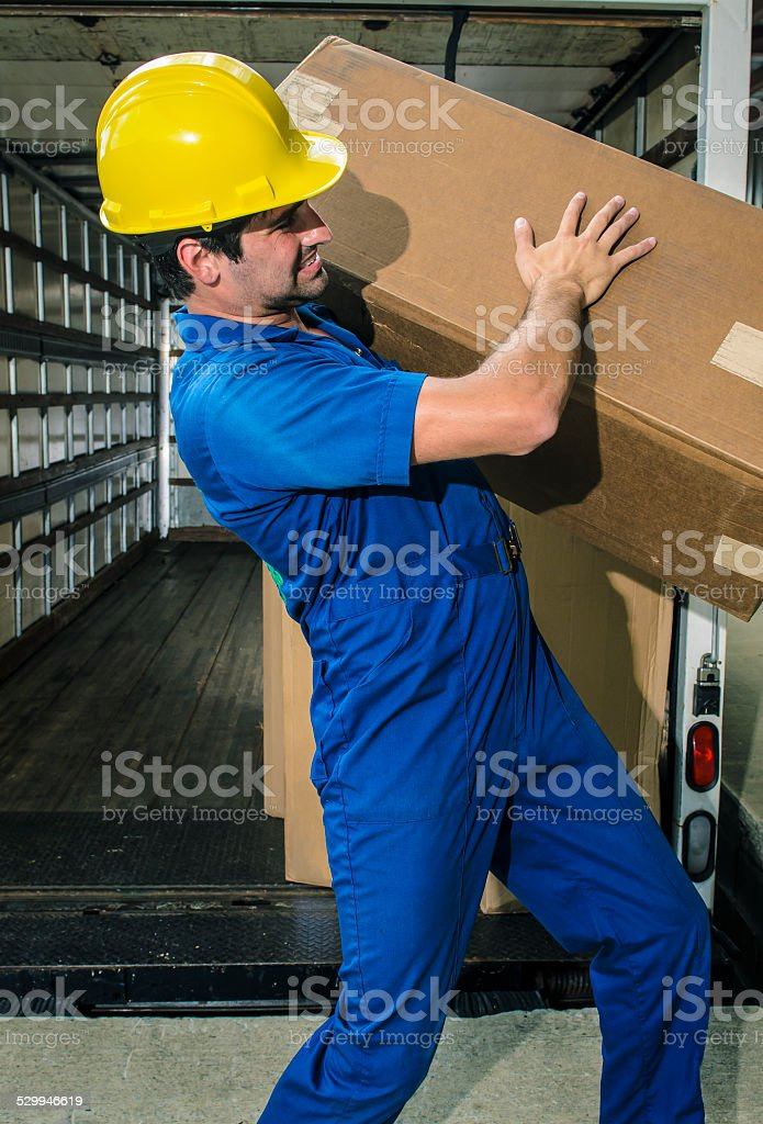 Young Man Carrying a Heavy Box stock photo