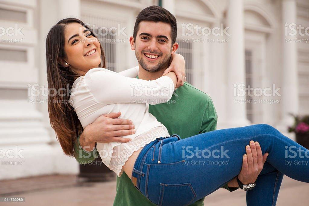 Young man carrying girlfriend and having fun stock photo