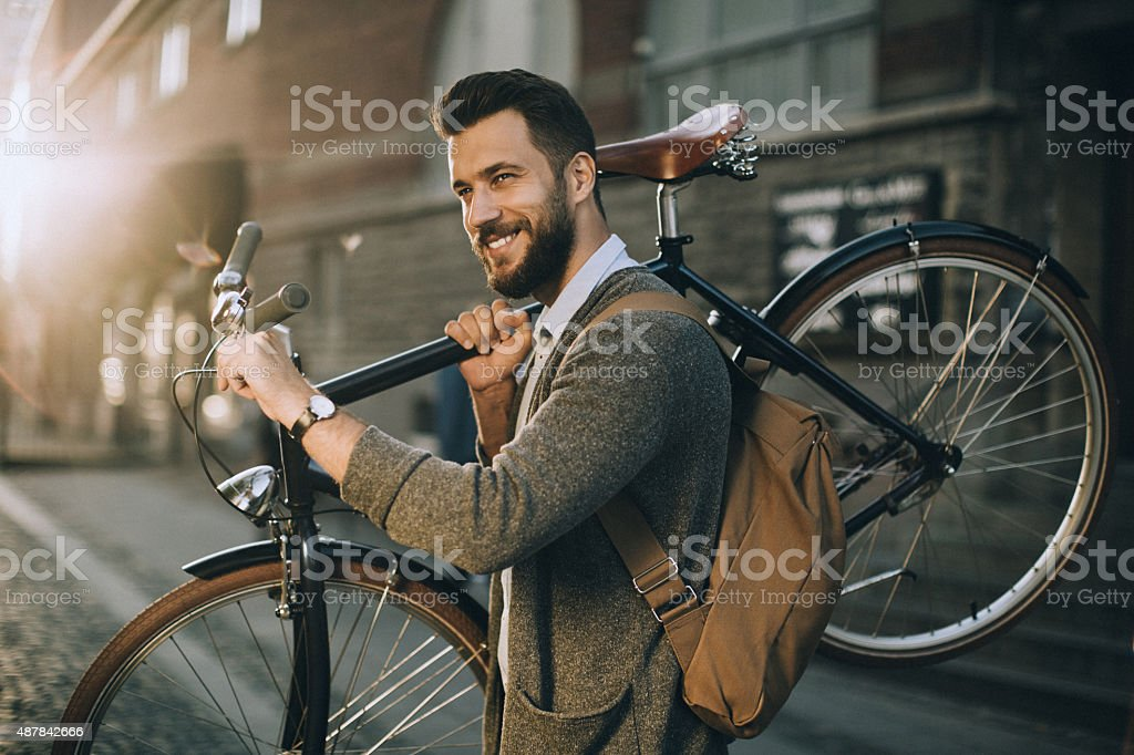 Young man carrying his bicycle stock photo