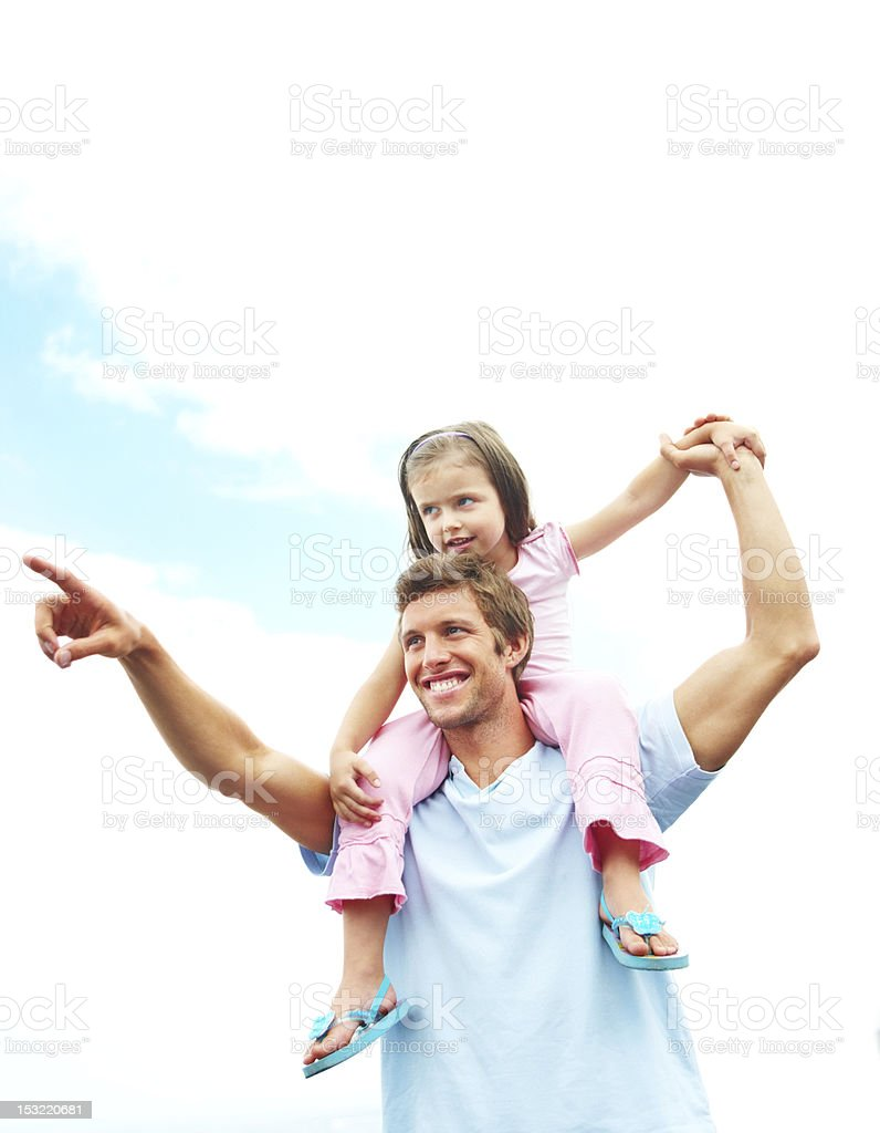 Young man carrying his daughter on shoulders and pointing away royalty-free stock photo