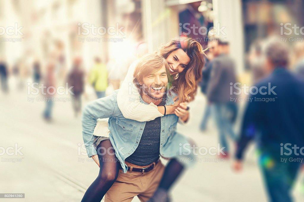 Junger Mann mit seiner Freundin in Huckepack nehmen – Foto