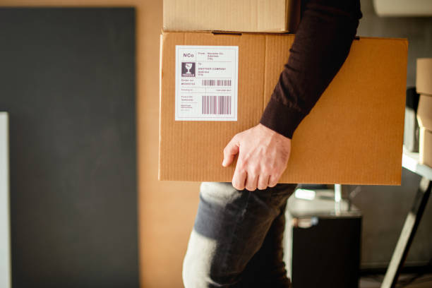 Young man carrying packages for shipment stock photo