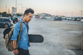 Young man carrying skateboard