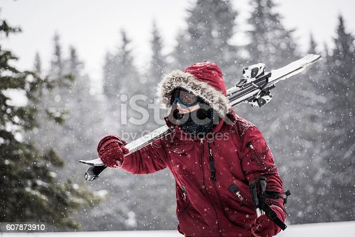 Young skier walking through snowy forest.