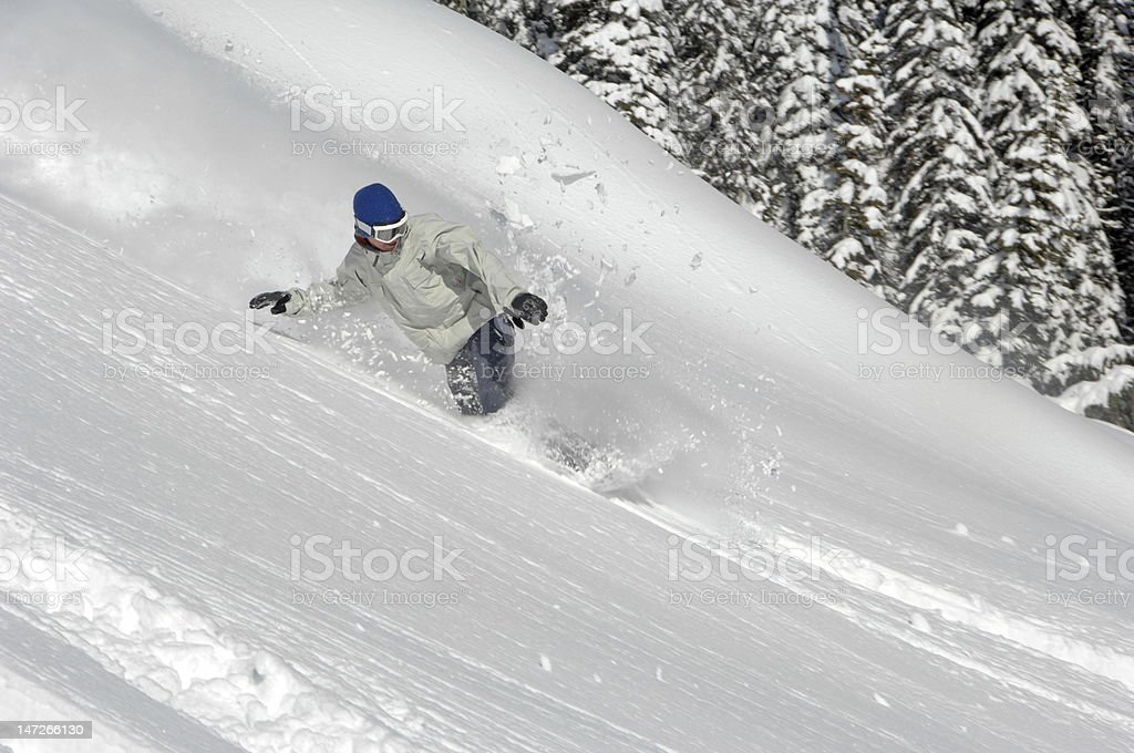 Young man carving through a powder turn on his snowboard stock photo