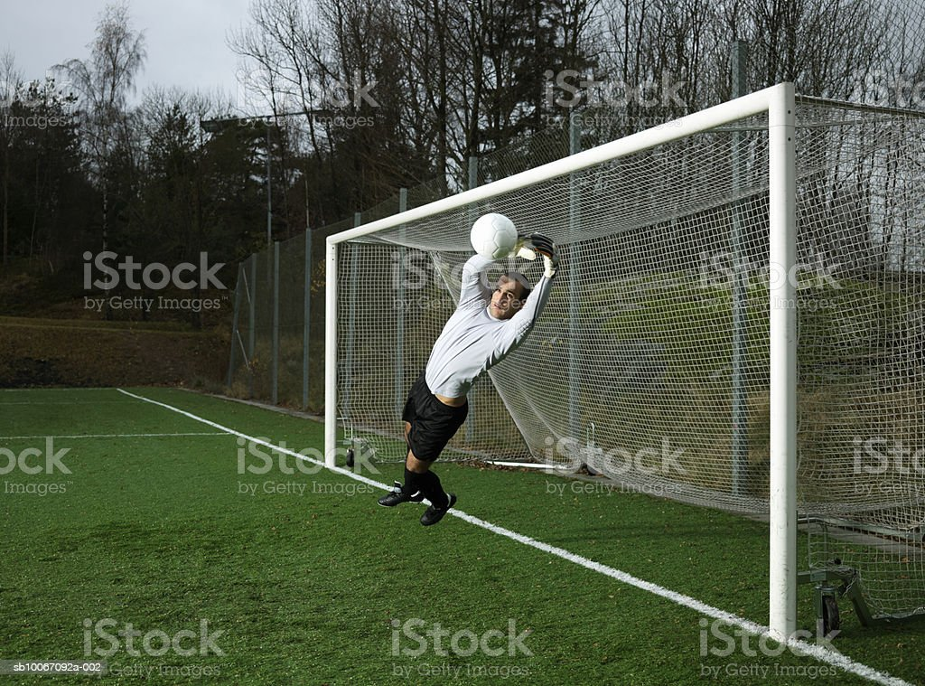 Young man catching ball at goal post royalty-free 스톡 사진