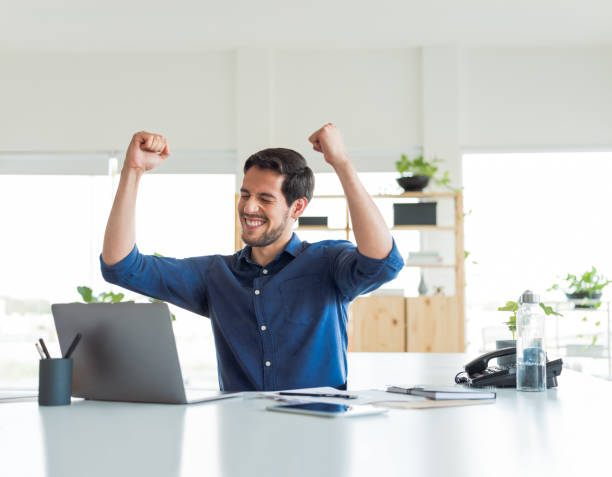 Young man celebrating in office stock photo
