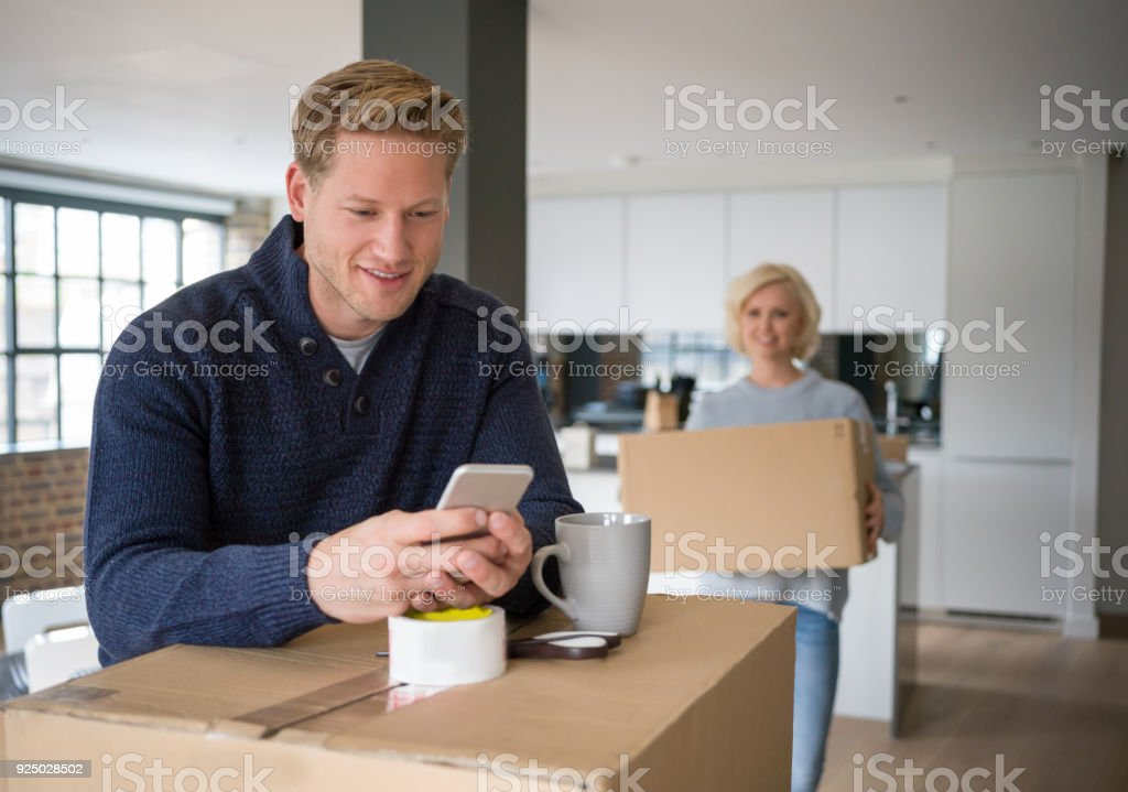 Young man chatting on his smartphone smiling while leaning on boxes...