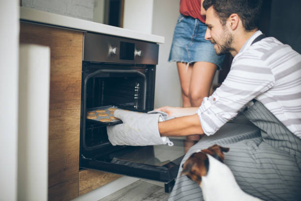Young man checking food in oven low angle view stock photo