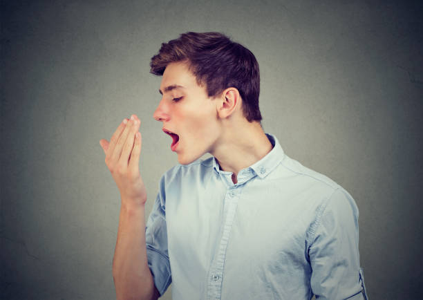 Young man checking his breath with hand. stock photo