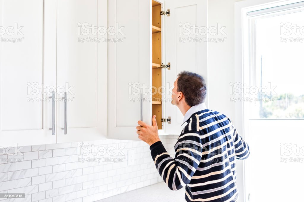 Young man checking looking inside empty kitchen modern cabinets by window after or before moving in stock photo
