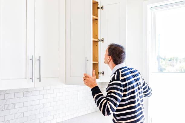 ung man kontrollera titta inuti tom moderna köksluckor av fönster efter eller före inflyttning - looking inside inside cabinet bildbanksfoton och bilder