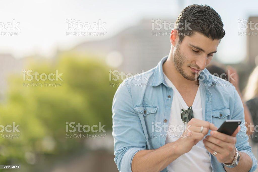 Junger Mann, die Nachrichten auf seinem Smartphone – Foto