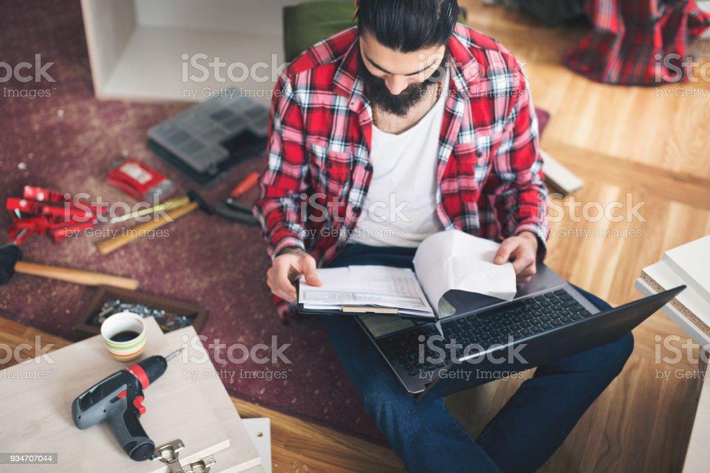 Junger Mann prüfen Pläne zur Herstellung von neuen Möbeln – Foto
